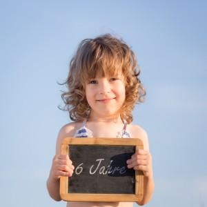 Happy child holding blank blackboard